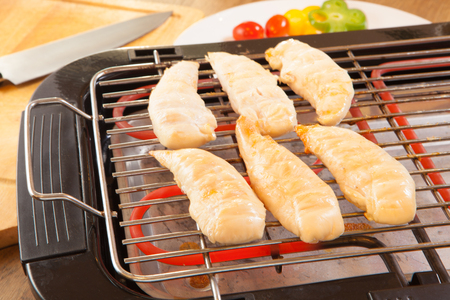 chicken breasts fillet on electric barbecue and grill