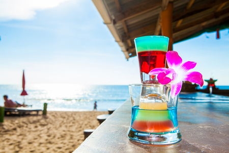 rainbow cocktail tower on beach, blue sea and sky background