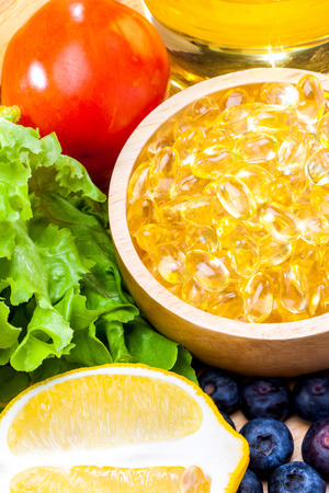 Fish oil, soft capsule, omega 3, supplement food vitamin D capsules with vegetables and fruit greens tomato lemon blueberry on wood .still life of healthy food and supplementary  diet concept closeup Banco de Imagens - 104111391