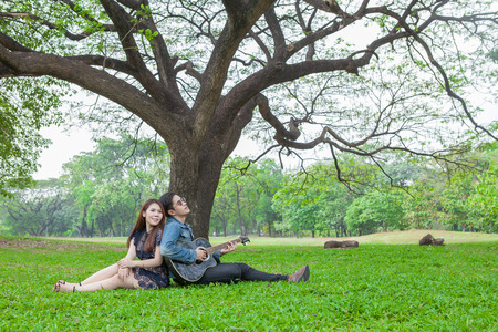 asian young couple in love enjoy playing guitar under a big tree in the park