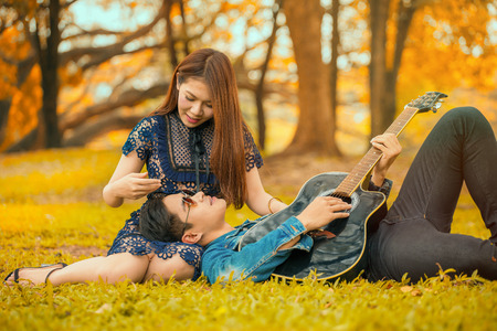 asian young couple in love enjoy man playing guitar lying on girlfriend legs in the garden autumn park with sun light Imagens