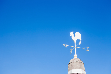 White rooster weather vane on blue sky