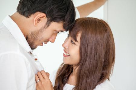 Jeune couple amoureux se regardant. femme aidant son mari à s'habiller dans un moment romantique du matin