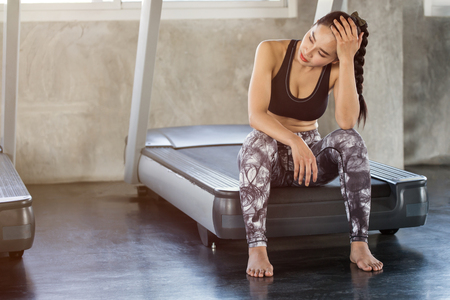 Beautiful Asian young woman tired taking a break from running or exercise sitting on treadmill machine  in fitness gym healthy .girl in sportswear workout rest in morning