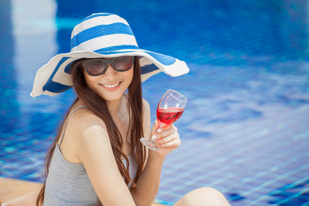 beautiful Young Asian women with beverages on summer party near the swimming pool .Happy girls in big hat and glasses relaxing with cocktail glass chilling , Stok Fotoğraf