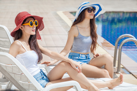 two beautiful Young Asian women in big summer hat and sunglasses sitting on sunbed by  swimming pool together . happy girl relaxing sunbathe Stok Fotoğraf