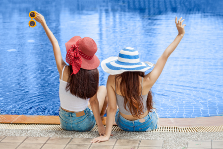 Back view of  two beautiful Young Asian women in big summer hat and sunglasses sitting on the edge of the swimming pool with feet in water together . happy girl relaxing kicking feet splashing water.