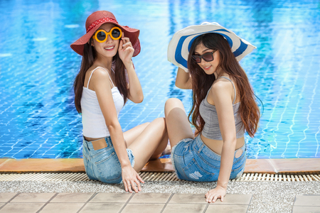 two beautiful Young Asian women in big summer hat and sunglasses sitting on the edge of the swimming pool with feet in water together . happy girl relaxing kicking feet splashing water.