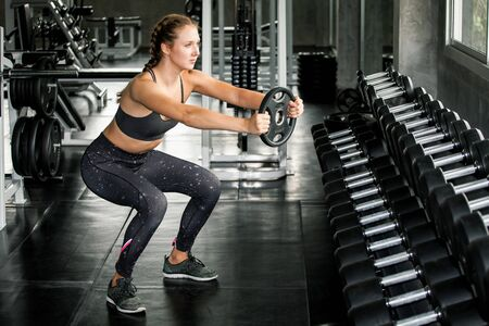 young fitness sport girl doing exercise squat with weight barbell plate in gym.woman in sportswear workout strengthen pumping up the muscles Stok Fotoğraf