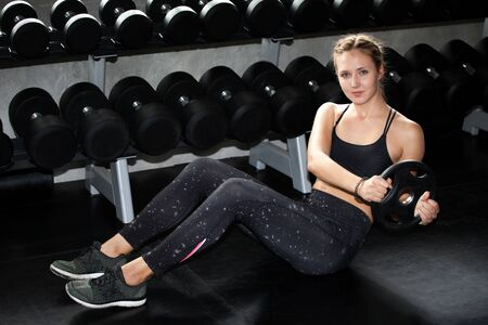 young fitness sport girl doing abdominal exercises with weight barbell plate in gym.woman in sportswear workout sit ups strengthen pumping up the muscles on floor