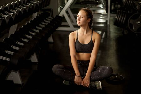 Beautiful young woman taking a break from exercise sitting cool down relaxation in fitness gym healthy .girl in sportswear workout rest near dumbbells shelf in morning