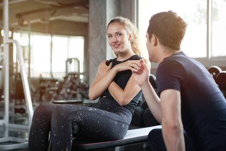 young sport woman exercise doing sit ups on the bench in fitness gym healthy .Muscular girl in sportswear training abs with trainer man workout.bodybuilding six pack Stok Fotoğraf