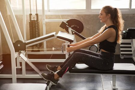 young fitness woman in sportswear exercising building muscles with machine Cable Crossover in sport gym morning ligth.workout