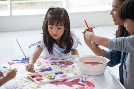 group of Cute little girl student painting  together with nursery teacher in classroom school . Happy children in a kindergarten Stok Fotoğraf