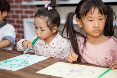 group of Cute little girl and boy student blowing color pen painting  together with nursery teacher in classroom school . Happy children in a kindergarten . kid artist multiethnic Stok Fotoğraf