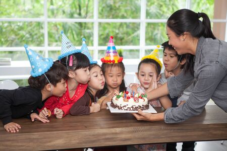 group of happy children girl with hat blowing candles on  birthday cake together celebrating in  party . kids gathered around  birthday cake with nursery teacher in classroom school multiethnic
