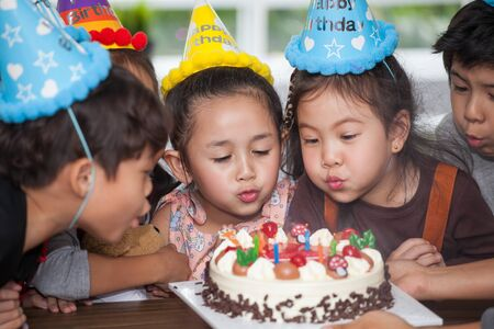 group of happy  children with hat blowing candles on  birthday cake together celebrating in party . adorable kids gathered around birthday cake multiethnic