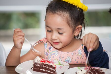 Little girl with hat eating birthday cake