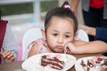 Little girl with hat bored eating birthday cake
