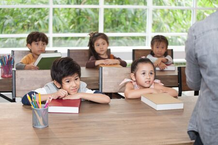 group of cute happy little child student leaning on table with book in classroom elementary school . kid clever sitting at desk preschool . Early education . Children smiling in kindergarten.