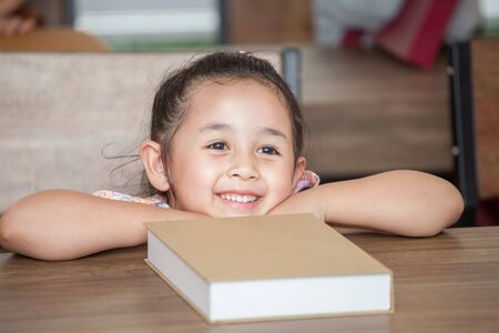 Cute happy little girl student leaning on table with book in classroom elementary school . kid or child clever sitting at desk preschool . Early education . Children smiling in kindergarten. Stok Fotoğraf