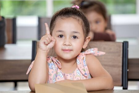 Cute little girl student pointing finger up in classroom school . Genius kid. Great idea . child clever sitting at desk preschool . Early education . Children in kindergarten.intelligence