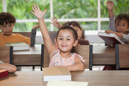 group Cute little girl student raising hands in classroom school . genius kid hand up . Great idea . child clever sitting at desk preschool . Early education . Children in kindergarten .multiethnic