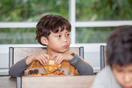 boy Children enjoy eating pizza in classroom school . kid hungry