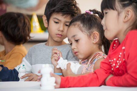Group of Cute little girl student painting a ceramic pottery model  in classroom school . kid artist . child sitting at desk preschool . Early education . Children in kindergarten . multiethnic