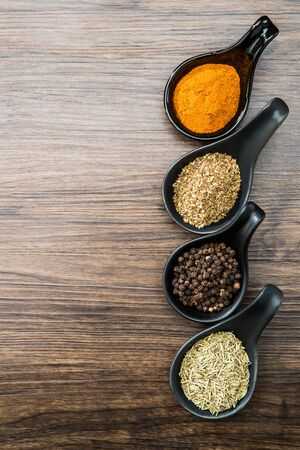 different spices and herbs in spoons or bowls on a brown wooden background . Food and cuisine ingredients with copy space .Dried rosemary,black pepper,red paprika powder or Cayenne Pepper ,oregano  Stok Fotoğraf
