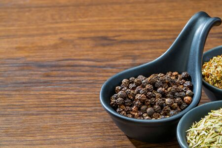 different spices and herbs in spoons or bowls on a brown wooden background . Food and cuisine ingredients  .Dried rosemary,black pepper,red paprika powder or Cayenne Pepper ,oregano close up