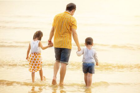 Father And Children  walking into the  Beach Holiday .  two kids one dad . rear back view Stok Fotoğraf