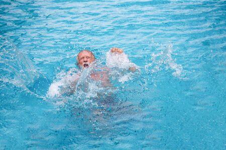 Senior man drowning  in swimming pool.