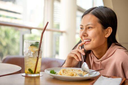 Happy smiling asian woman eating Italian pasta with lemonade in restaurants .