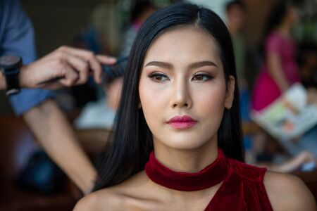 Hair stylist man making hairstyle to young beauty model on Backstage , asian woman Stock Photo