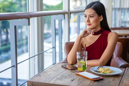 Beautiful young asian woman in red dress sitting in the restaurant looking out the window . happy elegant lady sitting on table thinking and waiting in date  Stok Fotoğraf