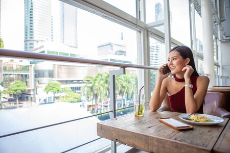 Beautiful young asian woman in red dress sitting in the restaurant looking out the window calling with smartphone . happy elegant lady sitting on table thinking and waiting in date  . copy space