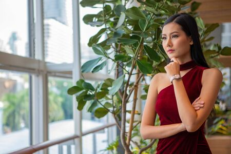 portrait of Beautiful young asian woman in red dress standing and looking out the window . elegant lady model thinking and waiting in date .sad , bored , late ,serious, angry girl posing hand on chin