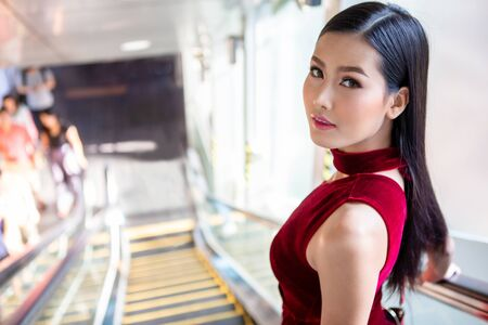 Beautiful young asian woman in red dress going down the escalator in shopping mall . happy elegant lady . copy space