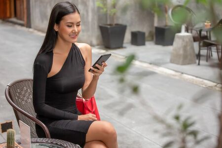 Beautiful young asian woman in black dress sitting in the coffee cafe  calling with smartphone . happy elegant lady sitting on table using mobile phone Stok Fotoğraf - 133957255