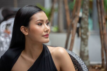 Portrait of  beautiful  young asian woman in a black dress looking away in city outdoor