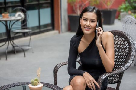 Beautiful young asian woman in black dress sitting in the coffee cafe  calling with smartphone . happy elegant lady sitting on table using mobile phone. Stok Fotoğraf