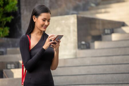 portrait of Beautiful young asian business woman in black dress calling with smartphone standing in the city . happy elegant lady model  using mobile phone in morning , outdoor . copy space