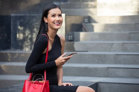 portrait of Beautiful young asian business woman in black dress calling with smartphone sitting in the city . happy elegant lady model  using mobile phone in morning , outdoor . copy space
