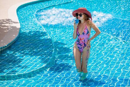 beautiful Young sexy woman wearing bikini with sunglasses and red hat drinking cocktail in swimming pool. Pretty girl in swimsuit posing and  relaxing at the poolside outdoor ,sunny day,summer Stok Fotoğraf
