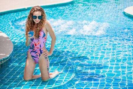 beautiful Young sexy woman wearing bikini with sunglasses drinking cocktail in swimming pool. Pretty girl in swimsuit posing and  relaxing at the poolside outdoor ,sunny day,summer Stok Fotoğraf
