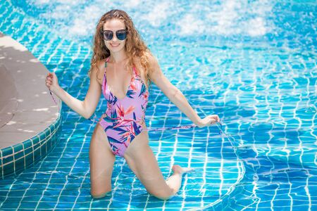 beautiful Young sexy woman wearing bikini with sunglasses in swimming pool. Pretty girl in swimsuit posing and  relaxing at the poolside outdoor ,sunny day,summer