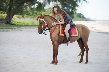 Woman riding a horse on sand beach in summer time