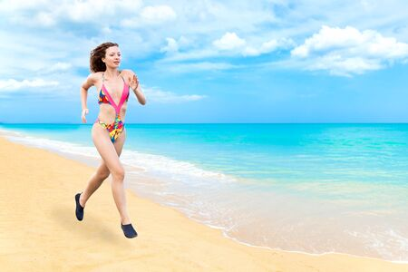 beautiful Young sexy woman wearing bikini running on the sand beach . fitness girl in swimsuit exercise or workout by the sea on blue sky , outdoor ,sunny day , summer