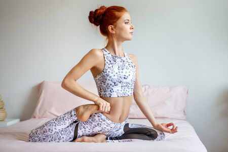 Young fitness woman in sportwear practicing yoga on bed in bedroom at home in Morning . sport girl doing One Legged King Pigeon Pose exercise indoors. workout healthy lifestyle . training. stretching